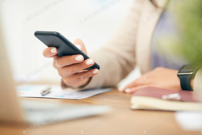 Close Up Businesswoman Holding Smartphone at Desk