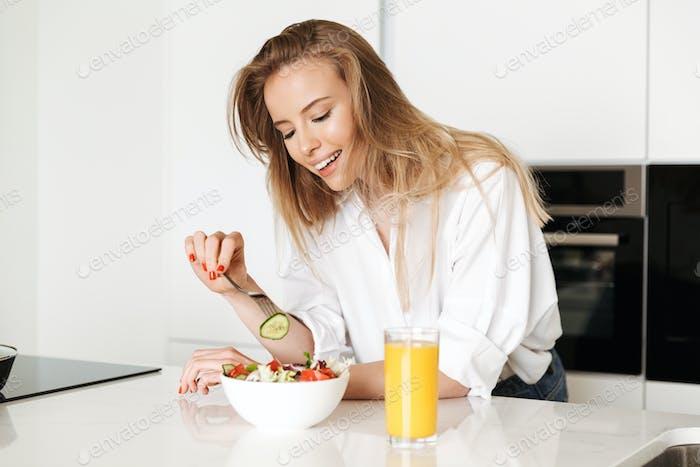 Улыбающаяся молодая женщина ест салат из миски