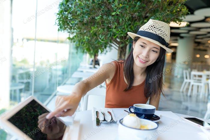 Woman order on tablet inside cafe
