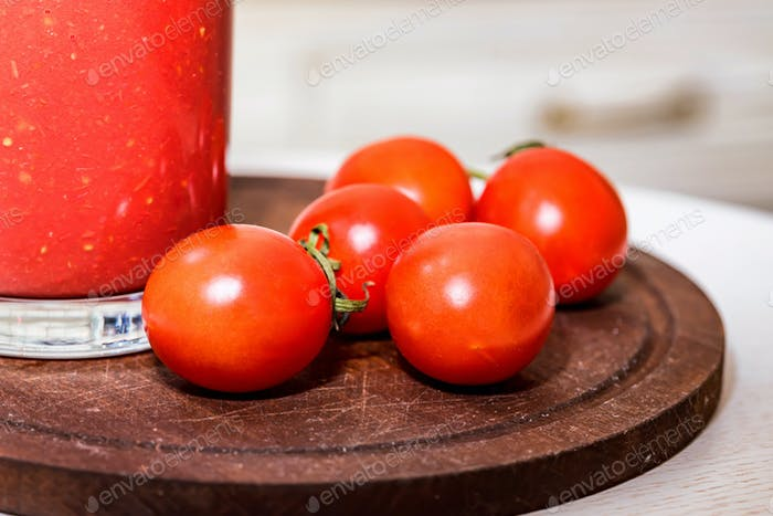 Glass bottle of tomato juice with fresh tomatoes