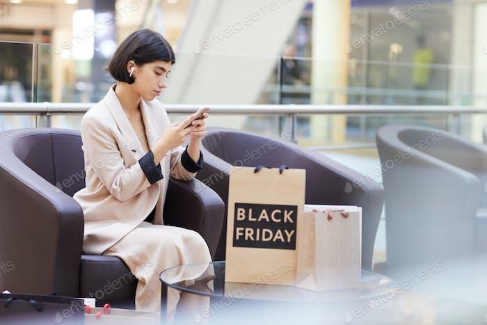 Geschäftsfrau mit Smartphone während der Entspannung im Einkaufszentrum