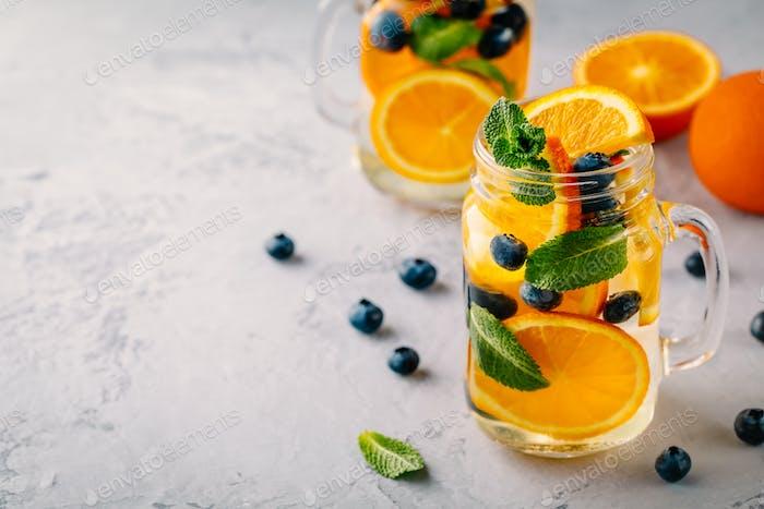 Infundiertes Detoxwasser mit Orange, Heidelbeere und Minze. Eiskalter Sommer Coctail oder Limonade.