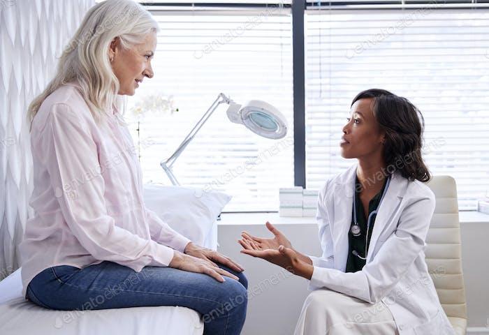 Reife Frau in Absprache mit weiblich Arzt sitzen auf Untersuchung couch in office