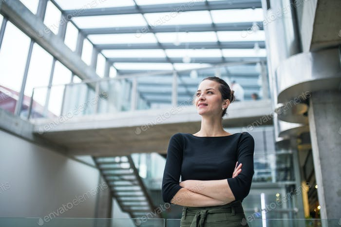 A portrait of young businesswoman standing in corridor outside office, arms crossed.