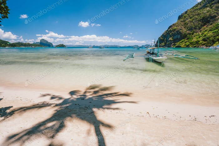 Beautiful scenery of Corong Corong beach with traditional boat and palm shadow. El Nido, Palawan