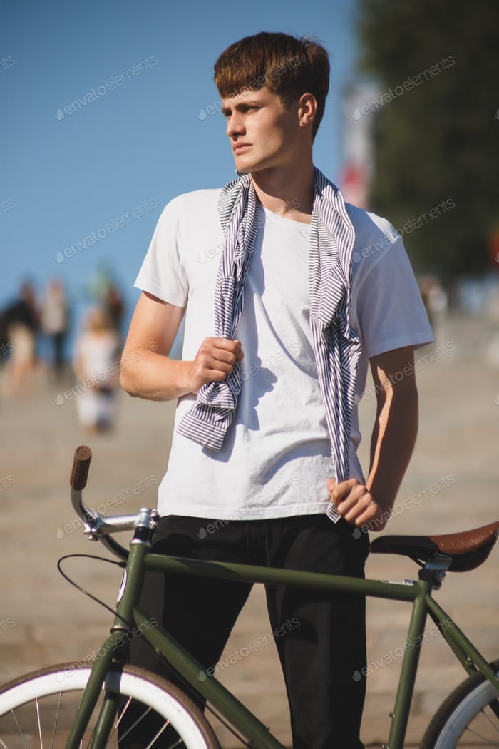 Photo of young thoughtful man in white t-shirt standing with bicycle on city background
