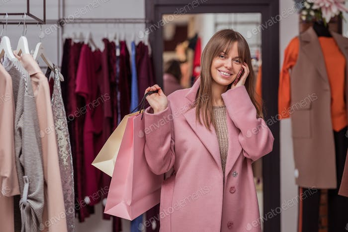 Smiling girl with shopping bags and a phone