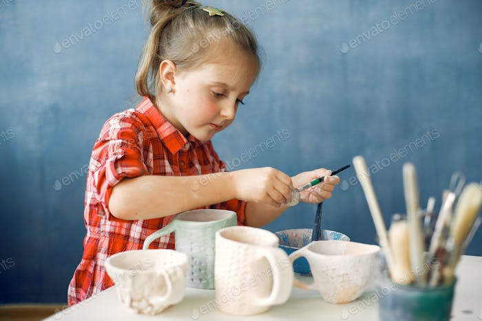A little girl painting dishes in a pottery