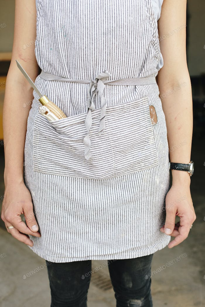 A woman in a workshop wearing a blue cotton apron with a chisel in the pocket.
