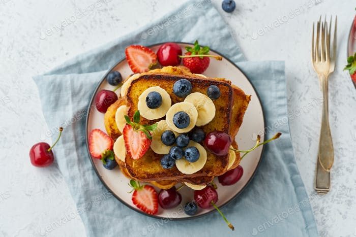 French toasts with berries and banana, brioche breakfast, white background, top view