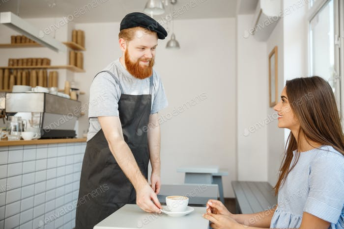Coffee Business Concept - Waiter or bartender serving hot coffee and talking with caucasian