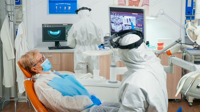 Stomatologist in coverall and patient looking at digital dental x-ray