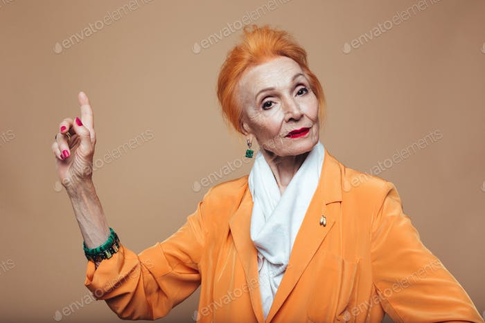 Attractive mature redhead fashion woman pointing