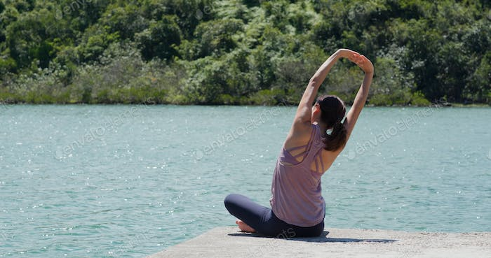 Woman do yoga and sit at lake side
