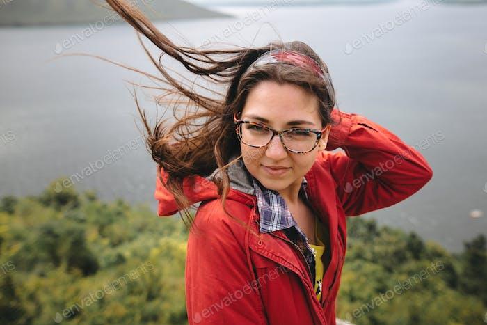Reisemädchen in rotem Regenmantel und mit windigem Haar stehend auf dem Felsenberg
