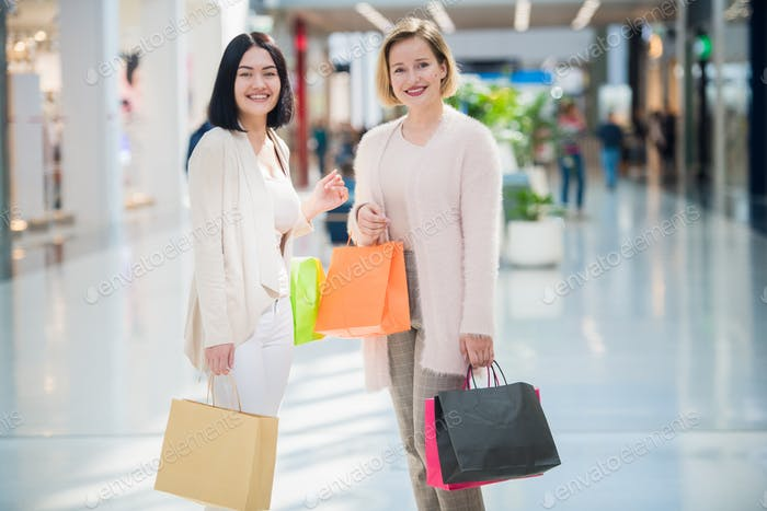 Girls standing and talking in shopping mall gallery