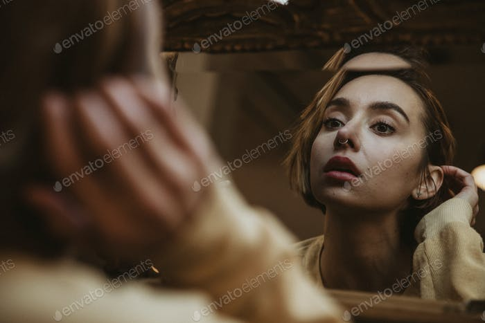 Woman looking in a mirror desolately