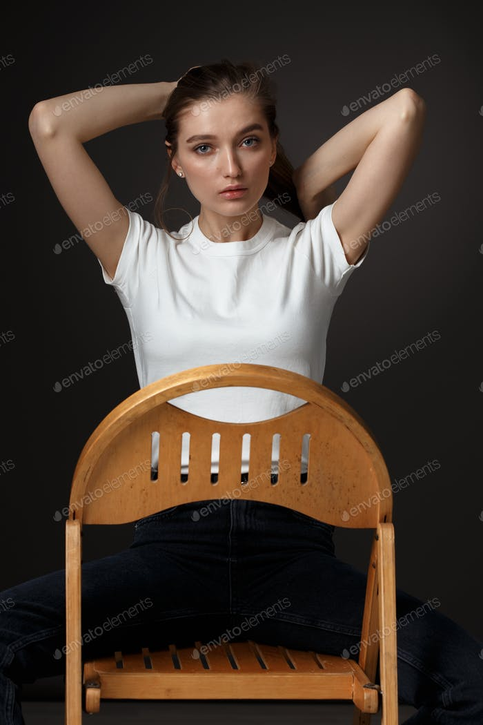 Charming brunette girl with long flowing hair dressed in white t-shirt and jeans poses sitting on