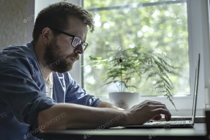 Concentrated bearded man in glasses works with a laptop at home