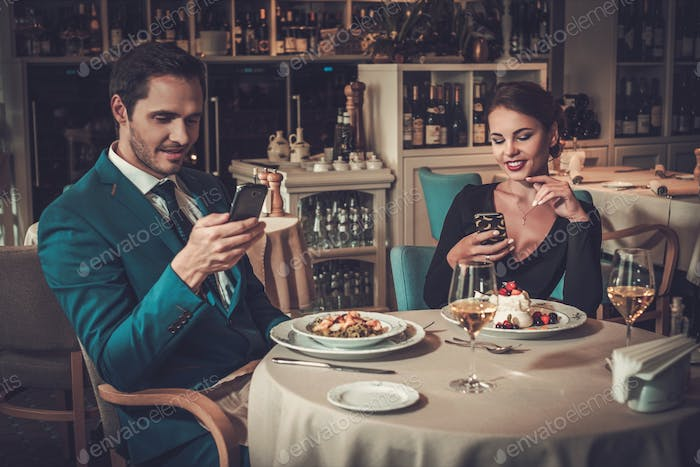 Stylish couple with mobile phones in a restaurant