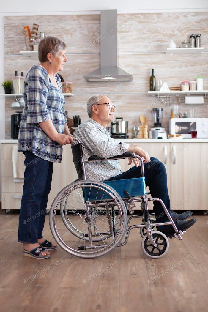Wife pushing invalid senior dreamy man in wheelchair in kitchen