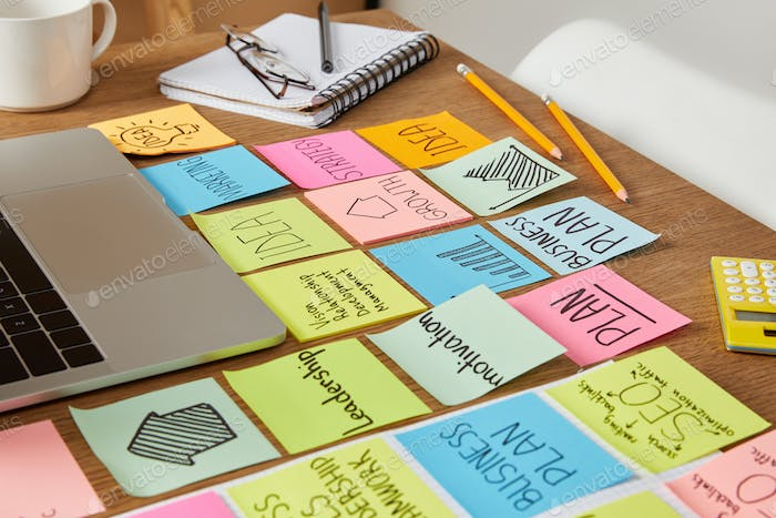 paper stickers with business strategy and laptop on tabletop
