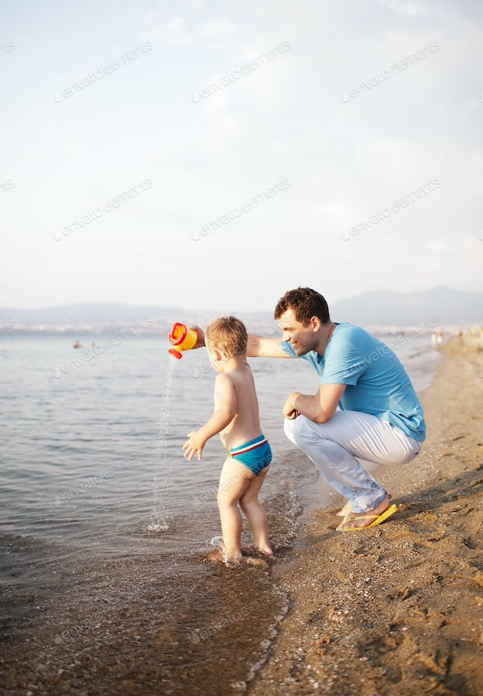 Young father playing with his son at the beach