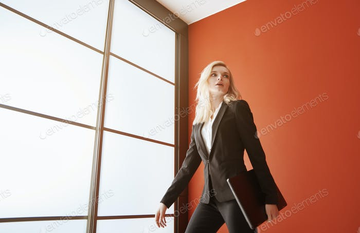 Young adult business woman wearing formalwear and carrying the laptop
