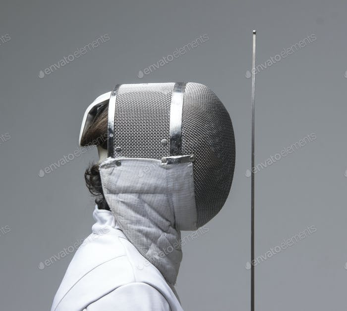 Profile of a fencer in fencing mask with the sword.Studio shot