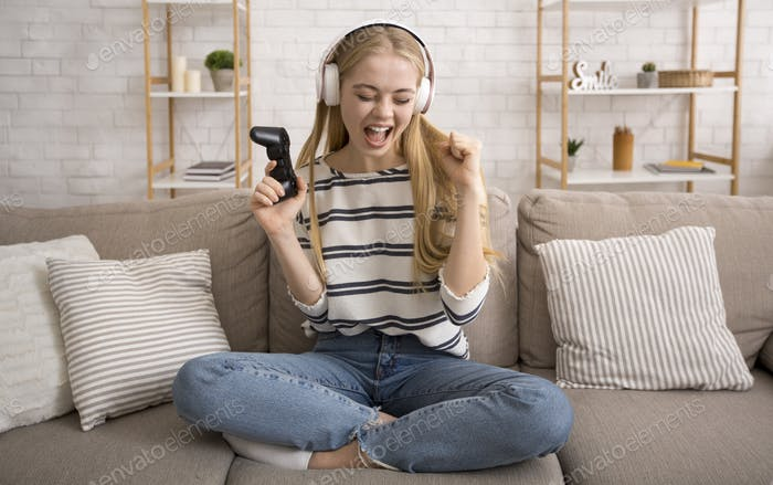 Pretty blonde girl playing video games at home