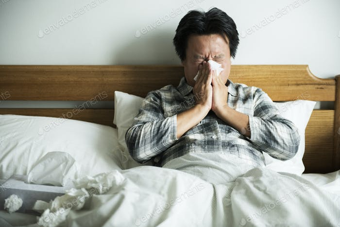 A man suffering from flu sitting in bed