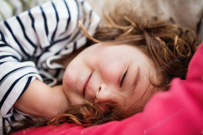 Ein kleines glückliches Mädchen im gestreiften T-Shirt zu Hause schlafen.
