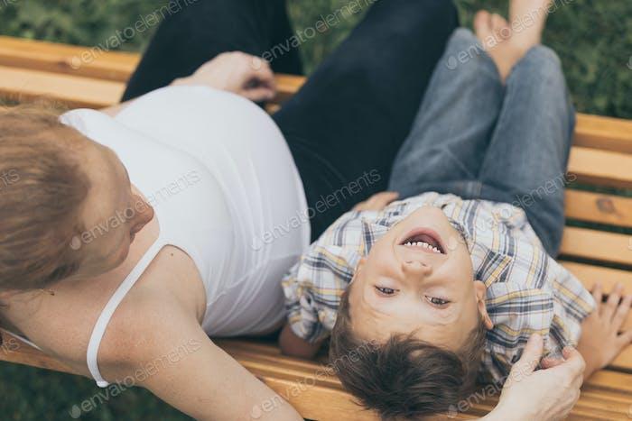 Glücklicher kleiner Junge umarmt Mutter im Park zur Tageszeit.