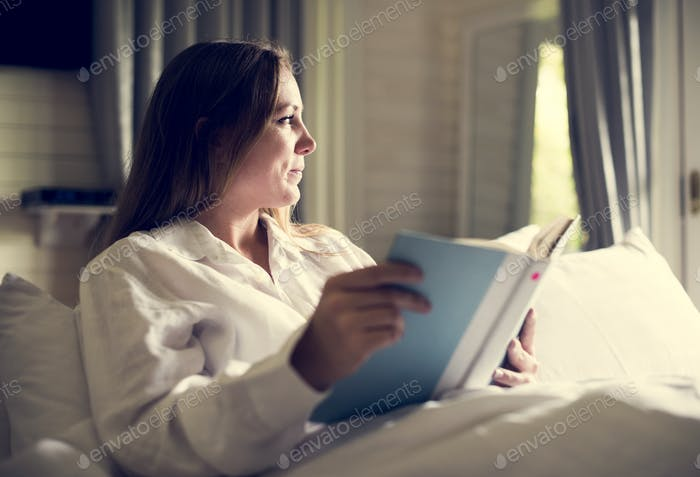 A Caucasian woman is reading a book