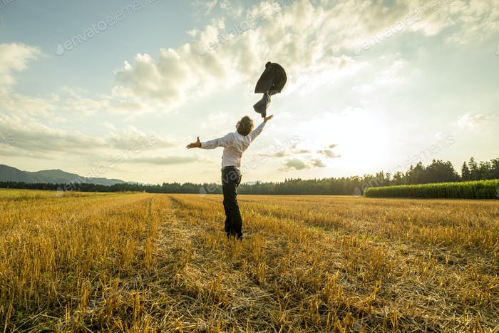 Businessman in field throwing jacket in air
