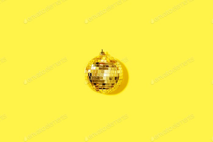 Creative Christmas composition. Flat lay, top view. Disco ball bauble on yellow background with copy