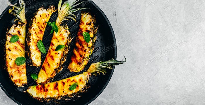 Grilled pineapple with fresh mint in cast iron pan on gray stone background.