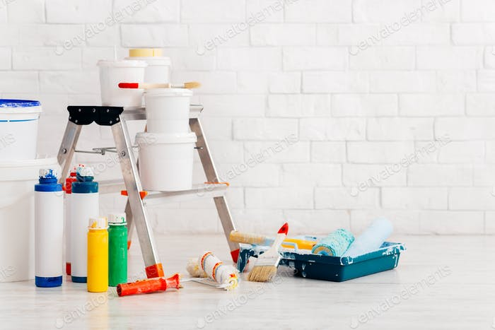 Painting supplies with ladder and paints against bricks wall