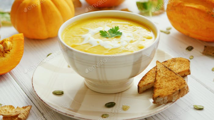 Pumpkin soup in bowl served with bread