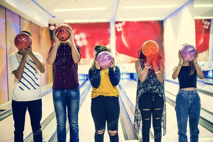 Friends bowling together indoors