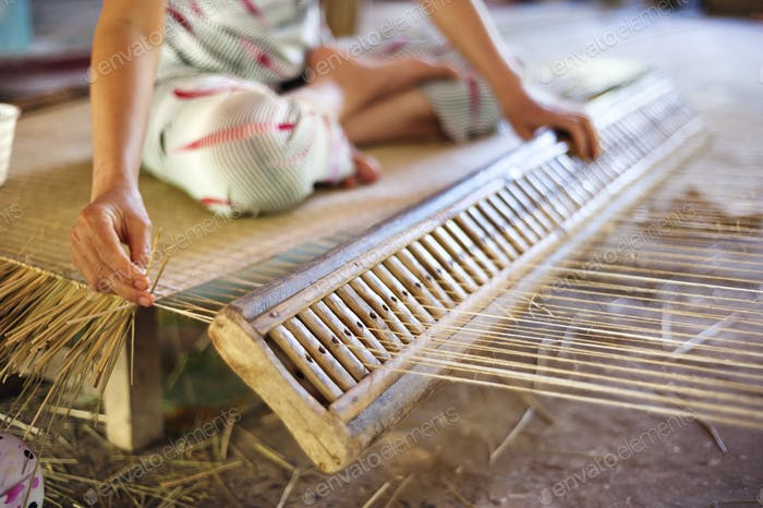 Vietnamese woman weaving a mat