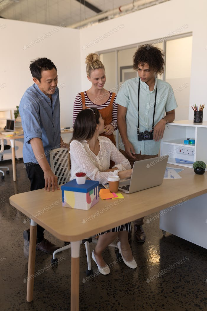 Side view of diverse business colleagues discussing plans over laptop in modern office