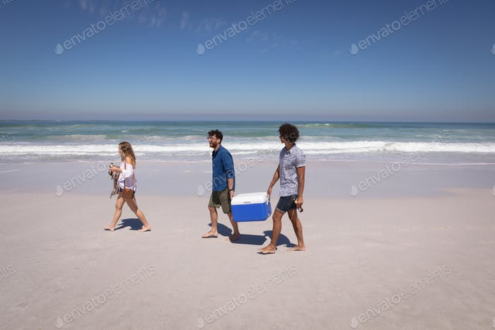 Group of friends carrying ice box and beer bottles while walking on the beach