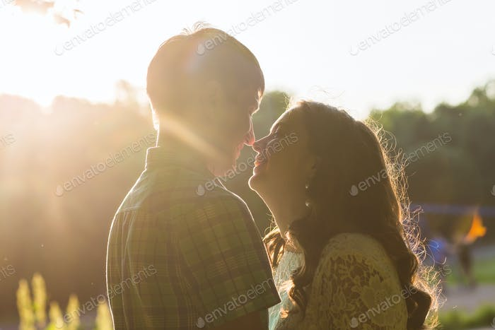 Closeup photo of romantic couple outdoors, side view.