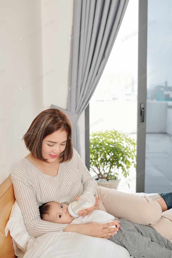 Woman feeding daughter with formula