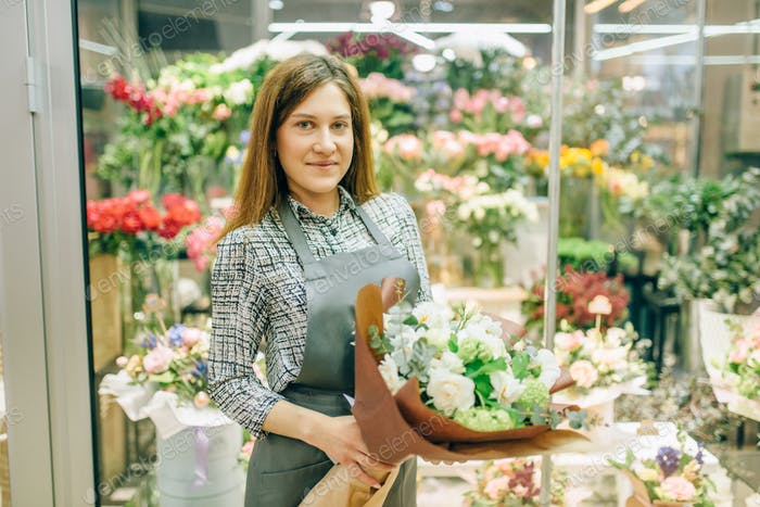 Florist in apron with fresh bouquet in flower shop