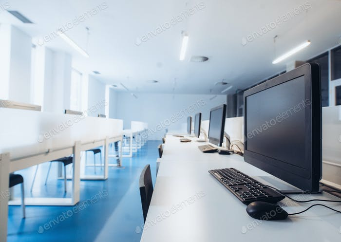 An interior of a modern spacious computer room in a library or office.