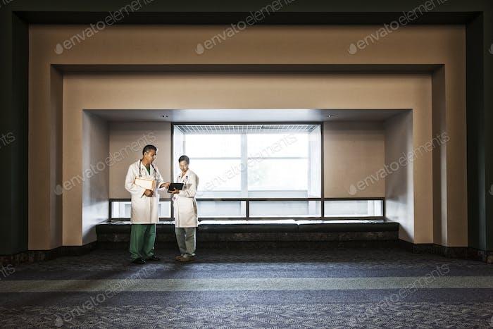 Kaukasischen Mann Arzt und asiatische Frau Arzt Verleihung im Krankenhaus Flur.