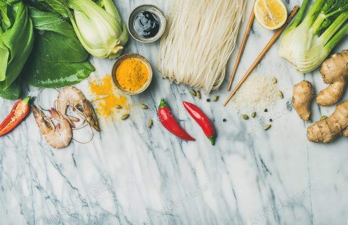 Flat-lay of Asian cuisine ingredients over marble background, copy space