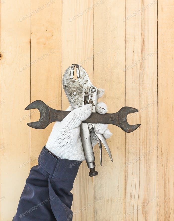 Hand in glove holding Spanner and Adjustable wrench